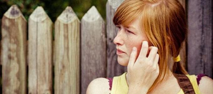 Женщина чешет ухо