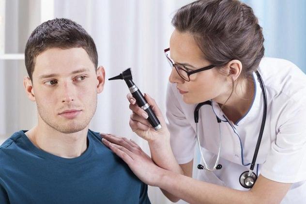 Врач осматривает ухо пациенту