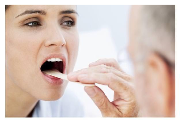 Доктор осматривает пациентке горло