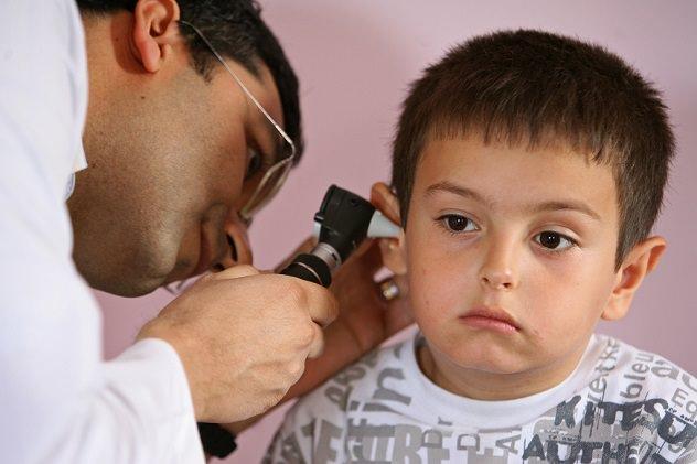 Врач осматривает ухо ребенку