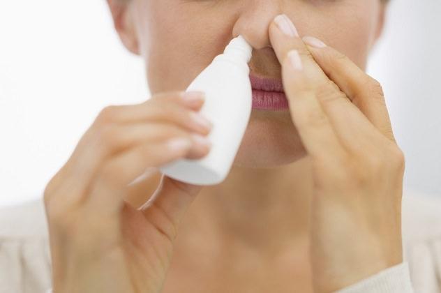 Женщина закапывает лекарство в нос