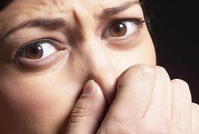 Женщина зажала свой нос