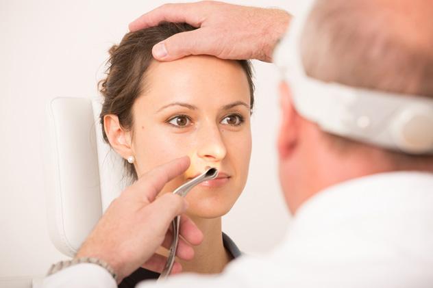Врач осматривает нос пациентке
