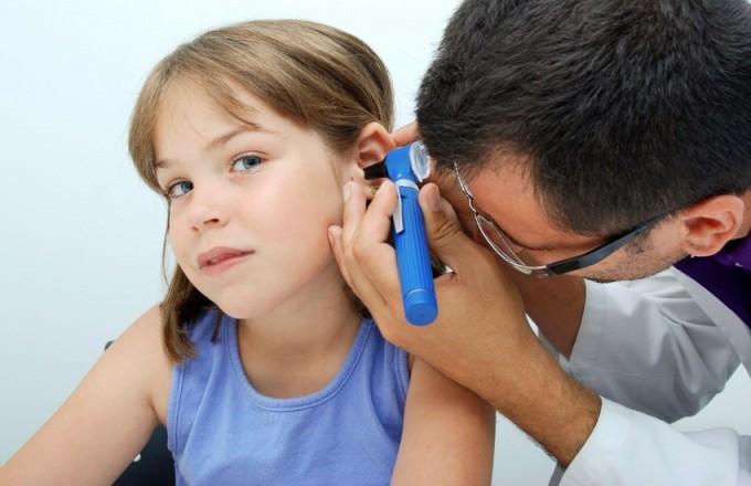 Врач осматривает ухо у девочки