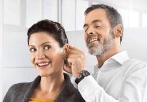 Доктор примеряет пациентке слуховой аппарат